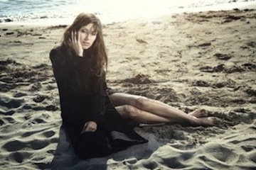 8908447-sad-woman-in-the-black-coat-sitting-on-the-sand-at-the-autumn-beach-natural-light-and-colors